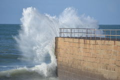 Crashing wave. Calm day with wave crashing over the end of the pier in Porthleven, Cornwall Royalty Free Stock Images