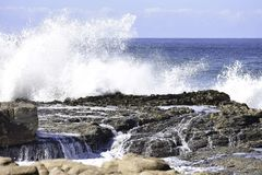 Crashing Wave And Flowing Water On Coastal Rocks, Uvongo, South Africa. Waves crashing and flowing over the life filled rocks on the humid South African Natal royalty free stock photo