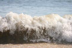 Crashing waves. Waves crashing on the sandy beach Stock Photos