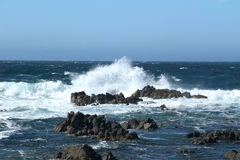 Crashing waves. Waves crashing against the rocks with a bright blue sky in the background and churning water around the dark gray rocks Royalty Free Stock Photo