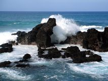 Crashing Waves. Waves crashing against some rocks off the coast of Maui Stock Images