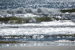 Crashing waves on a beach in Florida. Background of crashing waves on a beach in Florida with the sun shining on the water Royalty Free Stock Image