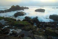 Crashing waves near Big Sur, California, USA. Sunset in fog over coastline near Hearst Castle, San Simeon, central California, USA Royalty Free Stock Image