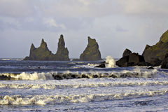 Crashing waves at Reynisdragar sea stacks. Waves crashing on rocky shore before sea stacks under early morning light stock images