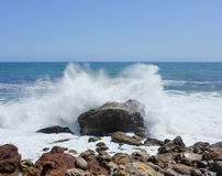 Crashing waves on a rock. Waves crashing on a rock violently stock photography
