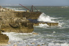 Crashing waves, rocks and a boat crane, Portland Bill. Portland Bill, Dorset, England, United Kingdom, boat crane and waves Stock Photos