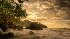 Waves crashing at Golden hour sunset in Costa Rica. Crashing waves on rocks in Manuel Antonio Costa Rica at sunset Stock Photography