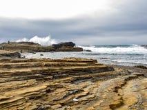 Crashing waves at rocky ocean cliffs Stock Photos