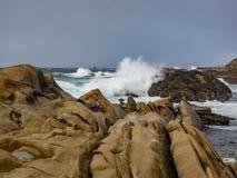 Crashing waves at rocky ocean cliffs Stock Photo