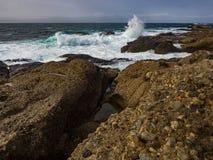 Crashing waves at rocky ocean cliffs Stock Photography
