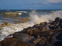 Crashing Waves. A rough ocean produces crashing waves on the rocks of the jetty at New Smyrna Beach in Florida stock photo