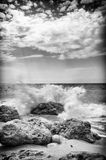 Crashing waves. Sun cloud cover wet rocks and salt wather droplets Royalty Free Stock Images