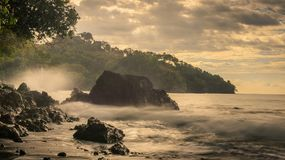Crashing waves at sunset in Costa Rica. Crashing waves in Manuel Antonio Costa Rica at sunset Stock Photos