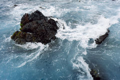 Crashing waves. Waves swell around a rock on the tenerife coastline Stock Image