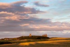 CRASTER, NORTHUMBERLAND/UK - 20 AOÛT : Coucher du soleil au-dessus de Dunstanburg images stock