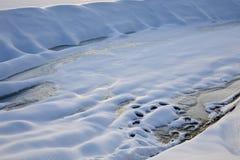 Cratère de neige sur une rivière congelée un jour ensoleillé d'hiver photographie stock