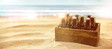 Crate of beers on a sunny tropical beach Stock Images