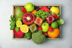 Crate with healthy detox smoothies and ingredients. On light background, top view Royalty Free Stock Photo