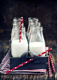 Crate of milk bottles with drinking straws Royalty Free Stock Images