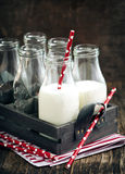 Crate of milk bottles with drinking straws in rustic style Stock Photos