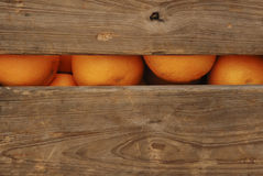 Crate of Oranges. Color image of oranges seen through a slot in the side of a wooden crate Stock Photo