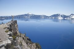 Crater Lake - Cliffside. Crater Lake National Park, showing a cliffside in the foreground with a small dead tree on top Royalty Free Stock Images
