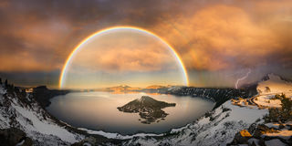 Crater lake with double rainbow and lightning bolt Royalty Free Stock Photo