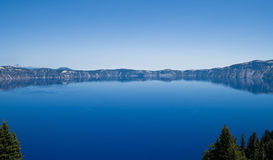 Crater Lake in Oregon. View of Crater Lake volcanic caldera in Oregon.  It is the deepest lake in the United States fed solely by falling rain and snow Royalty Free Stock Photography