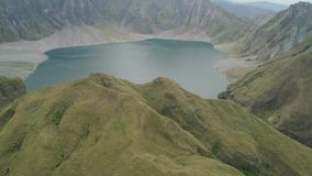 Crater Lake Pinatubo, Philippines, Luzon. Lake high in the mountains, aerial view. Beautiful mountain landscape with. Peaks of mountains and volcanoes. Mountain stock video