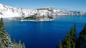 Crater Lake. A view of the island in Crater Lake with snow on the mountains Royalty Free Stock Image