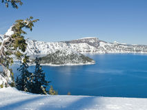 Crater Lake in winter. Mountain lake with snow and surrounding trees and Wizard Island at Crater Lake National Park, Oregon Stock Images