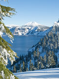 Crater Lake in winter. Mountain lake with snow and surrounding trees at Crater Lake National Park, Oregon Stock Photos