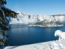 Crater Lake in winter. Mountain lake with snow and surrounding trees and Wizard Island at Crater Lake National Park, Oregon Royalty Free Stock Photos