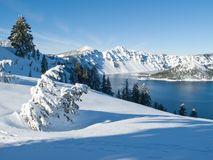 Crater Lake in winter. Mountain lake with snow and surrounding trees at Crater Lake National Park, Oregon Stock Photo