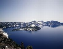 CRATER LAKE AND WIZARD ISLAND. Crater Lake with reflection  of surrounding snow covered hills in blue water of lake Royalty Free Stock Photo