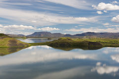 Craters covered with grass are reflecting in still water, Myvatn Royalty Free Stock Photo