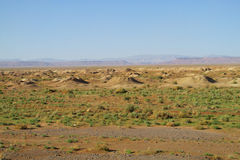 Craters in desert. Draw-well in the desert, poor green vegetation, mountains on horizon royalty free stock photography