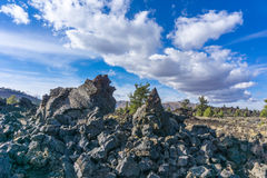 Craters of the Moon National Monument Vista with Sharp Rocks. Vivid blue sky and high white clouds over sharp rocks in the rugged lava fields in Craters of the royalty free stock image