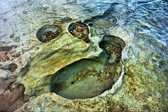 Craters on rocky sea beach Royalty Free Stock Photos