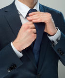 Cravat. Businessman dressed up the knot of his cravat Royalty Free Stock Photo