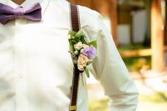 Cravatta a farfalla porpora di colore dello sposo con il boutonniere fotografia stock libera da diritti