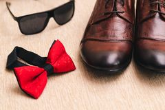 Cravatta a farfalla rossa, le scarpe degli uomini di cuoio marroni ed occhiali da sole sopra su una superficie leggera del tessut fotografie stock libere da diritti
