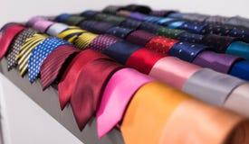 Cravatte sui ganci nel negozio di vestiti degli uomini Immagini Stock