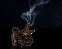 Craved Dragon Incense Burner Burning with Smoke Ri. Incense burner in the form of a carved wood dragon figurine on a black background.  The incense is burning in Stock Images