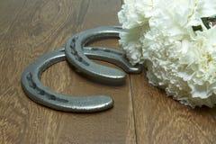 Cravos brancos para Belmont Stakes com as ferraduras na madeira Fotografia de Stock