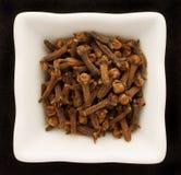 Cravos-da-índia da especiaria em uma bacia cerâmica. Fotos de Stock Royalty Free