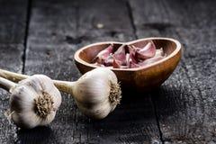 Cravos-da-índia de alho em uma tabela preta de madeira Bulbo fresco do alho com a imprensa de alho do ferro Fundo do vintage Faze Foto de Stock Royalty Free