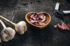 Cravos-da-índia de alho em uma tabela preta de madeira Bulbo fresco do alho com a imprensa de alho do ferro Fundo do vintage Faze Fotos de Stock Royalty Free