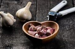 Cravos-da-índia de alho em uma tabela preta de madeira Bulbo fresco do alho com a imprensa de alho do ferro Fundo do vintage Faze Fotografia de Stock