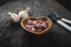 Cravos-da-índia de alho em uma tabela preta de madeira Bulbo fresco do alho com a imprensa de alho do ferro Fundo do vintage Faze Imagens de Stock Royalty Free